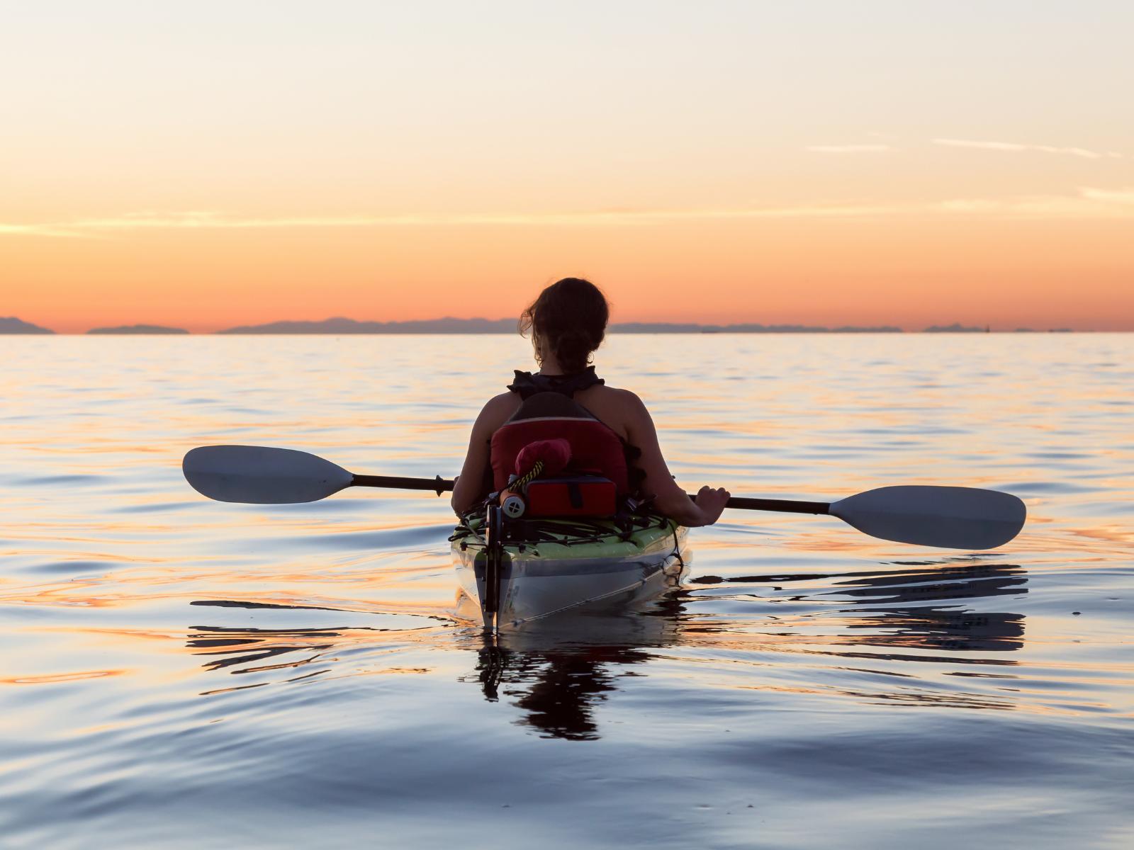 charleston-sc-kayaking woman in kayak on he water watching sunset